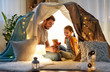 Leinwanddruck Bild - family, hygge and people concept - happy father with teddy bear toy and little daughter playing in kids tent at night at home