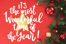 """Flat Lay With Pine Tree Branches With Red And Golden Christmas Balls And Golden Star Isolated On Red With """"its The Most Wonderful Time Of Year"""" Inspiration"""