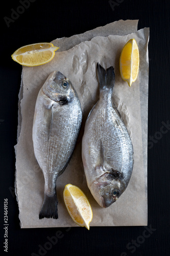Fotografie, Obraz Fresh dorado fish with lemon on baking sheet over dark background, overhead view