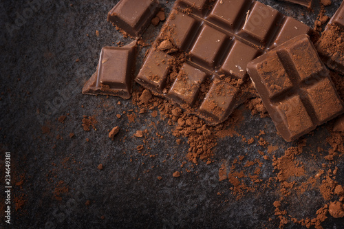 chocolate and cocoa powder on a dark slate background with copy space, high angle view from above