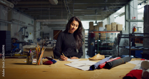 Portrait of professional fashion designer drawing a new shoe model according to the Italian tradition Fototapeta