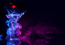 Cherry Falling Into A Martini Splashing On Blue And Purple Smoky Background