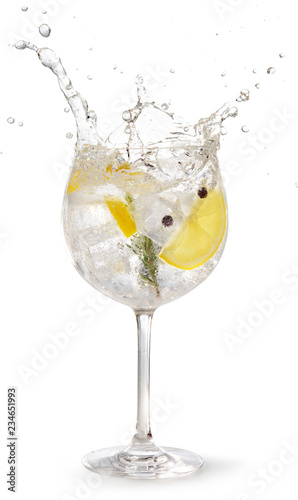Spoed Foto op Canvas Cocktail gin tonic garnished with lemon and rosemary splashing on white background