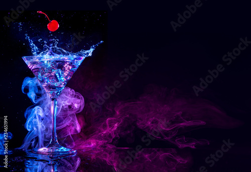 Cadres-photo bureau Cocktail cherry falling into a martini splashing on blue and purple smoky background