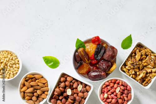 Various Nuts in a ceramic bowl and Dried Fruits on a light stone table. The Concept of a Healthy Dessert. Top view flat lay background. Copy space.