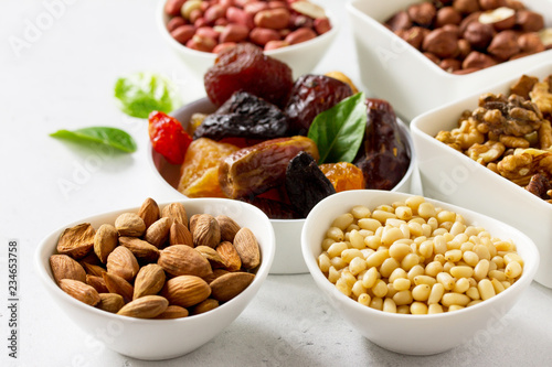 Various Nuts in a ceramic bowl and Dried Fruits on a light stone table. The Concept of a Healthy Dessert.