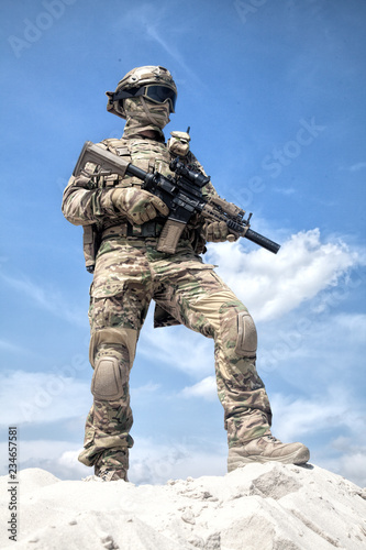 Valokuvatapetti Man in military camouflage uniform and mask, equipped tactical ammunition, standing on sand dune with service rifle replica in hands, cloudy sky on background