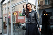 canvas print picture - Pretty indian girl in black saree dress and leather jacket posed outdoor at street.
