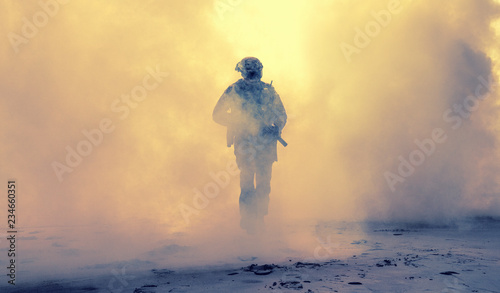 Fotografie, Obraz Special operations forces soldier, army ranger or commando in camo uniform, helmet and ballistic glasses walking at battlefield covered with smoke