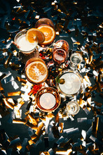 Flat Lay With Various Alcoholic Cocktails And Party Horns On Table Covered By Golden Confetti