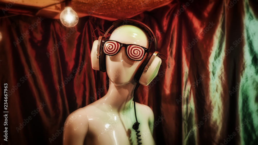 Hypnotic glasses and vintage headphones on a female mannequin. - obrazy, fototapety, plakaty