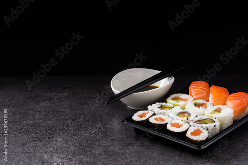 sushi assortment on black tray and soy sauce. Copyspace