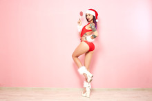 Charming Girl With Purple Hair Tips And Tattoos On Her Arms Dressed In Red Swimsuit, Santa's Hat, White Fur Bracelets And High Heels Holds A Lollipop On The Background Of Pink Wall