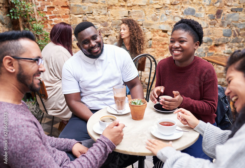 Friends talking over coffee in a trendy cafe courtyard