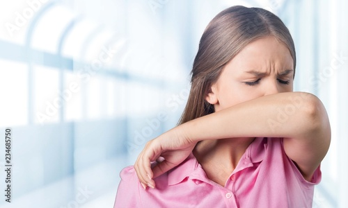 Leinwand Poster Young woman scratching her nose with elbow on background