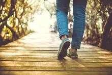 Man Is Walking On Small Wood Bridge To Nature Walk Way.