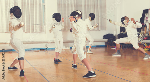 Boys and adults practicing fencing techniques - Buy this