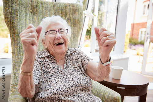 Fotografía  Portrait Of Excited Senior Woman Sitting In Chair In Lounge Of Retirement Home
