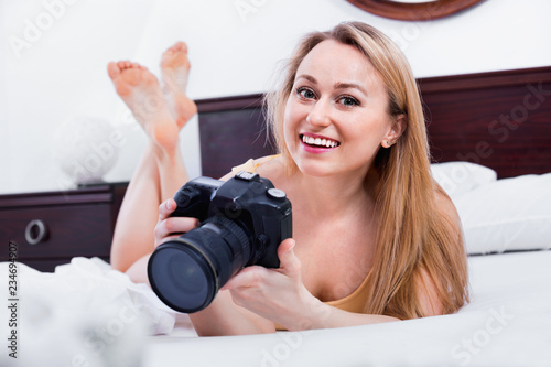 Poster Akt Laughing woman lying in the bed and holding a camera