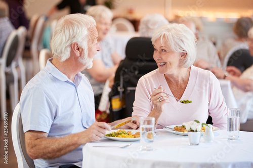 Senior Couple Eating Meal And Talking In Retirement Home