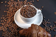 Close up of coffee cup and croissant in coffee beans on black background.