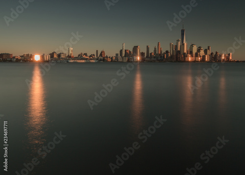 Fotografie, Tablou  View on fiance district in Manhattan from Hudson river at sunset with sun  refle