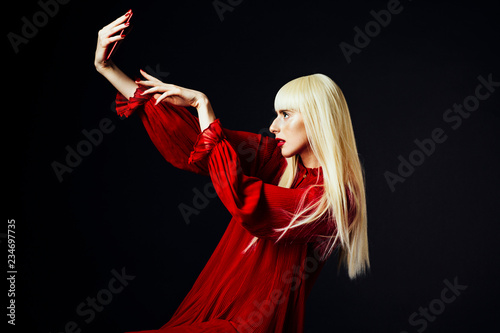 Portrait of a beautiful blonde woman holding a red smartphone about to press the button, isolated on black studio background