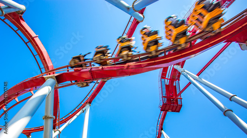 yellow roller coaster with people inside move fast, high speed, in roller rail i Wallpaper Mural