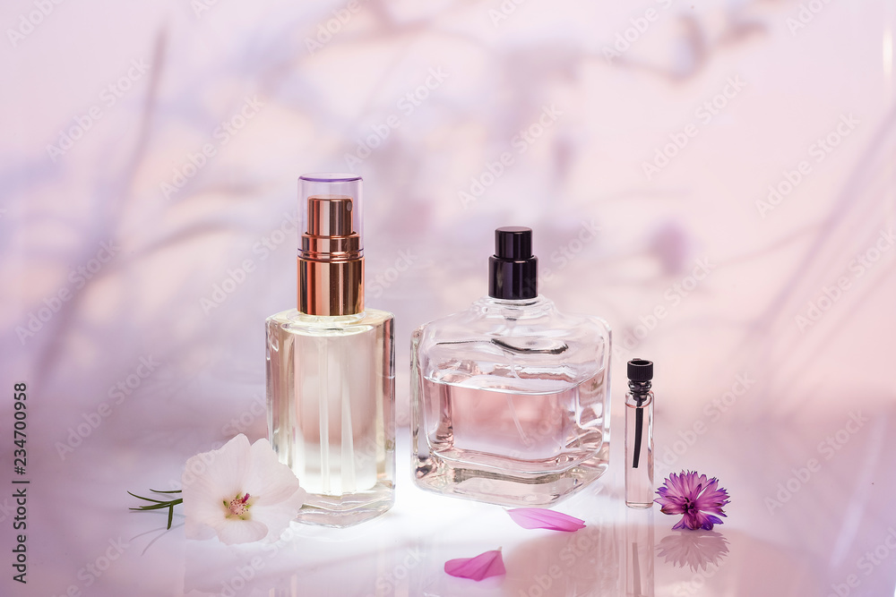 Fototapety, obrazy: Different perfume bottles and sampler with plants on a pink floral background. Selective focus. Perfumery collection,