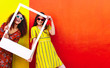 Leinwanddruck Bild - Girls looking through blank picture frame