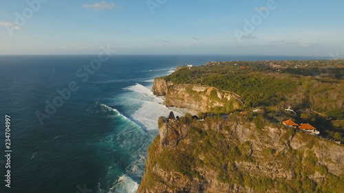 Aerial view of sea rocky coast with surf the waves, Bali, Indonesia, Pura Uluwatu cliff. Waves crushing rocky shore. Seascape, rocks, ocean. Travel concept.