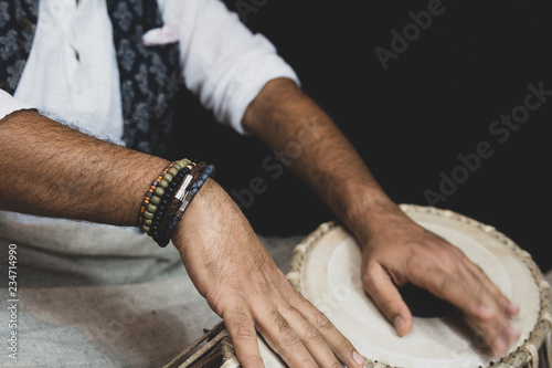 In de dag Boho Stijl Images of a man's hands (wearing beads) playing the Tabla - Indian classical music percussion instrument - black background.