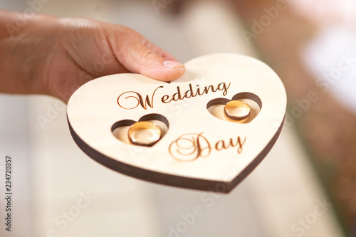 Fotografía  newlyweds wedding rings on a wooden heart-shaped stand in the church