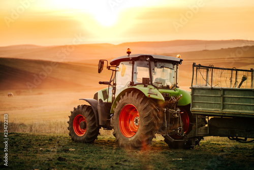 Photo Details of farmer working in the fields with tractor on a sunset background