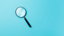 Magnifying Glass On Pastel Bac...