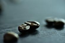 Focus Sur Un Seul Grain De Café Sur Un Fond De Nombreux Grains De Café Sur Un Tableau Noir De Pierre