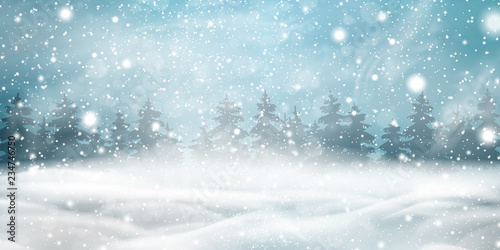 Natural Winter Christmas background with blue sky, heavy snowfall, snowflakes, snowy coniferous forest, snowdrifts. Winter landscape with falling christmas shining beautiful snow.