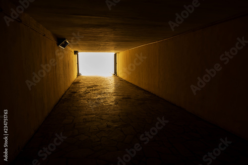 Long stone tunnel. Light at the end of the tunnel at the destination. Silhouettes in a tunnel against the background of light at the end of the road. Gloomy creepy picture as background for design.