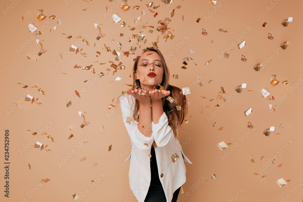 Fototapeta Portrait of happy lovely woman send a kiss to camera on isolated background with confetti. Happy celebration of new year, birthday
