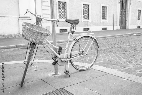 Old vintage bicycle tied to a pole on a sidewalk in the center of Rome, Italy. Ecological means of transport, without fuels and without emissions, no pollution. Healthy lifestyle.