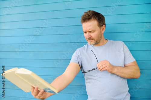 Portrait of mature man with big black eye glasses trying to read book but having Canvas Print