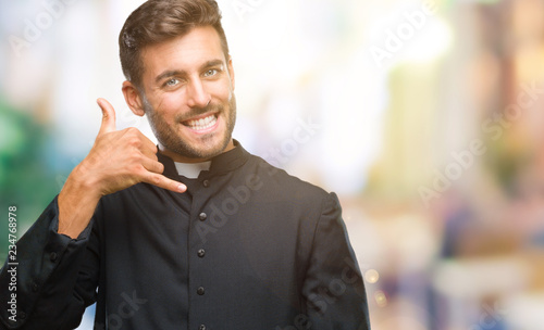 Fotografia Young catholic christian priest man over isolated background smiling doing phone gesture with hand and fingers like talking on the telephone