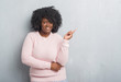 canvas print picture - Young african american plus size woman over grey grunge wall wearing winter sweater with a big smile on face, pointing with hand and finger to the side looking at the camera.