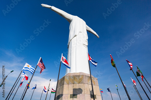 Poster Historisch mon. Cristo del Rey statue of Cali with world flags and blue sky, Colombia