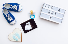 """Flatlay Pregnancy Composition With Space For Text On White Background. Top View Of Children's Accessories: Toys, Pacifier, Baby Screen, Baby Projector Lamp """"it's A Boy"""" And Delicious Gingerbread"""