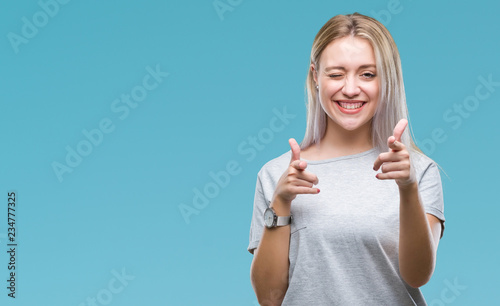 Fototapeta  Young blonde woman over isolated background pointing fingers to camera with happy and funny face