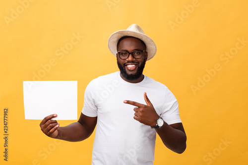 Photo Picture of young smiling african-american man holding white blank board and poin