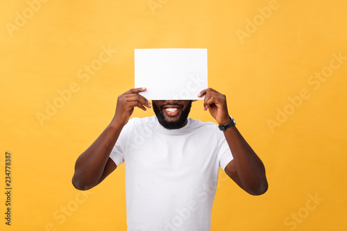 Fotografía  Young happy African-american hiding behind a blank paper, isolated on yellow bac