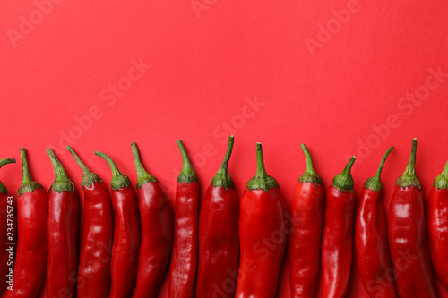 Flat lay composition with fresh chili peppers and space for text on color background