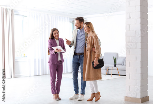 Female real estate agent working with couple in room Fototapete
